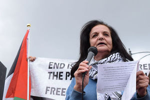 A Palestinian woman wearing a keffiyeh around her neck speaks to a crowd