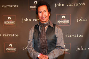 Alejandro Escovedo. Latinx man with black hair smiles in brown shirt and scarf and grey vest in front of brown wall with light brown text