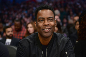 Chris Rock. Black man in black jacket and shirt smiles in front of blurry sports stadium audience and walls