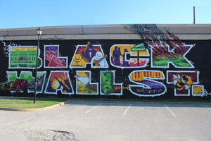 """Multicolored mural with block text reading """"BLACK WALL STREET"""" on black background on gray wall in front of blue sky and behind green grass and grey concrete"""