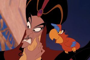 Jafar and Iago in Disney's Aladdin. Brown man in black and red turban and tunic grimaces as red bird sits on shoulder in front of blue and gold and brown background