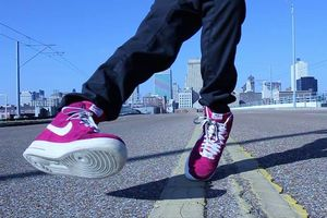 Feet in red and white Nike shoes and legs in black jeans dance on grey pavement in front of Memphis skyline and blue sky