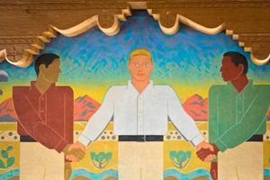 Mural depicting White man with blue eyes in White shirt holding hands of Indigenous and Latinx man without faces and in green and red shirts, respectively, in front of brown desert sand and blue sky