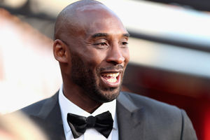 Kobe Bryant. Black man in black and white tuxedo in front of red and white background.