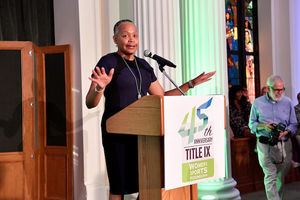 Lisa Borders. Black woman in purple and black dress speaks behind brown podium with white sign with blue and green text and in front of white columns and black curtains and brown barriers