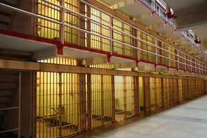 Image of empty row of jail cells, with dim lights glowing in each cell.
