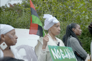 "A Black woman wearing all white holds a green sign that says ""No Goode Way"" and a red, black and green flag."