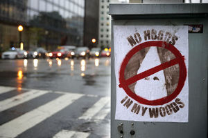 "Graffiti with white hood of Ku Klux Klan member in red circle with line through it on white flyer with brown text reading ""NO HOODS IN MY WOODS"" on grey pole and in front of grey street with cars and rain"