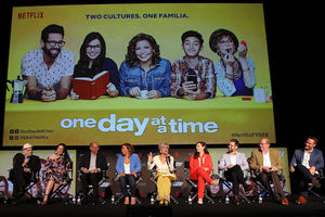 Norman Lear, Gloria Calderón Kellett, Mike Royce, Justina Machado, Rita Moreno, Isabella Gomez, Tod Grinnell, Stephen Toblowsky. White men and Latinx women on black stage in front of screen with yellow television show title card