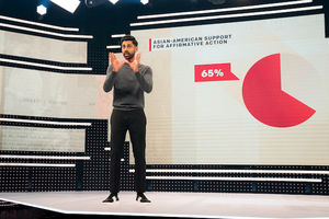Hasan Minhaj. Brown man with black hair and beard wears grey shirt and black pants and holds hands up in front of screen with pink chart and text and beige background
