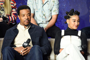 Russell Hornsby and Amandla Stenberg. Black man in navy jacket and beige shirt sits next to Black teenage girl in black shirt and white overalls in front of White people in multicolored clothing and blue curtain