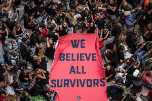 "Dozens of people hold and rally around a massive red sheet with ""We believe all survivors"" printed on it in navy blue."