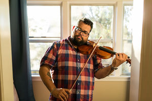 Vijay Gupta. South Asian-American man plays brown violin with brown bow in red and blue plaid shirt and blue jeans in front of beige wall and green curtain and green trees