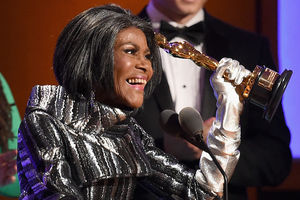 Cicely Tyson. Black woman with black hair in silver outfit and light grey gloves holds gold Oscar statue in front of black woman in green outfit and man in black and white tuxedo and purple and brown screens