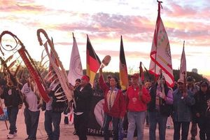 Indigenous people in multicolored clothing holding ceremonial flags and black and red and yellow flag of the American Indian Movement in front of brown rocky terrain and pink sky