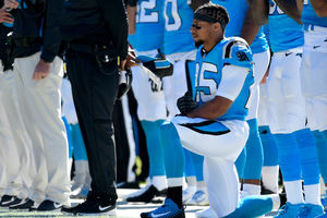Eric Reid. Black man in light blue and white football uniform kneels near men in similar uniforms.