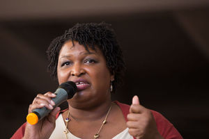 """Democratic gubernatorial nominee Stacey Abrams, wearing a red sweater and gold necklace, leads a """"March To The Polls"""" In Atlanta on October 28, 2018."""
