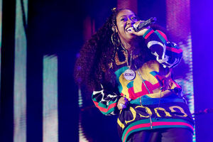Missy Elliott. Black woman with black hair in gold jewelry and black and red and green and yellow outfit holding black microphone in front of black and green and red screen