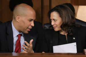 Cory Booker and Kamala Harris. Black man and woman dressed in black suits lean close and talk.