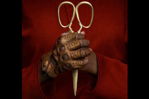Hands of Black person wearing one brown leather glove holds gold scissors while dressed in red robes
