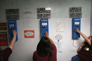 Three women in burgundy shirts sitting next to each other. They each make phone calls on blue telephones mounted on a wall with laminated signs including a plaque that says calls may be subject to recording.