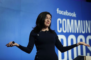 "Sheryl Sandberg. White woman in black dress shrugs shoulders in front of blue screen with white text that spells ""facebook COMMUNITY BOOST"""