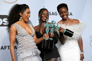 Angela Bassett, Lupita Nyong'o and Danai Gurira. Three Black women in grey, black and white dresses smile while holding green award statues in front of grey background with black text