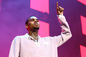 Chris Brown. Black man with black hair and tattoos holds up one finger in red and white shirt in front of pink and purple background
