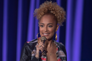 Amanda Seales. Black woman with blonde hair smiles in black and pink and blue jacket while holding black and grey microphone in front of dark blue curtain