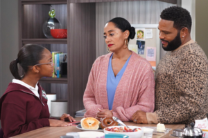 Marsai Martin, Tracee Ellis Ross and Anthony Anderson. Black girl in maroon hoodie speaks to Black woman in pink sweater and blue shirt and Black man in brown sweater around brown table and in front of grey walls and multicolored appliances