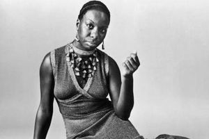 Nina Simone. Black-and-white photograph of Black woman lying on side in dress and multiple necklaces in front of gray background