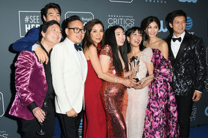 Ken Jeong, Chris Pang, Nico Santos, Michelle Yeoh, Awkwafina, Constance Wu, Gemma Chan and Harry Shum Jr. Asian women and men in multicolored formal attire smile around silver award statue in front of grey background with white logos