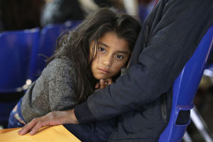 A 7-year-old girl with long, brown hair leans on her father as he sits in a blue chair at the Catholic Charities-run Humanitarian Respite Center after being released by U.S. Customs and Border Protection (CBP), on November 1, 2018.