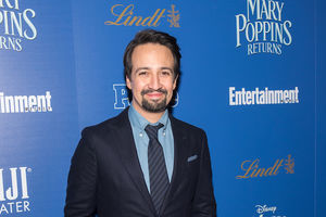 "Lin-Manuel Miranda. Latinx man with black hair and beard in dark suit with blue tie and shirt in front of blue wall with light blue text spelling ""MARY POPPINS RETURNS"" and white text spelling ""Entertainment"""