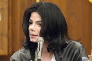 Michael Jackson. Man with black hair and white bleached skin sits in black leather jacket and white shirt in front of brown wood courtroom wall