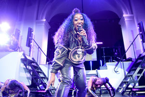 Missy Elliott. Black woman with black hair performs while clothed in black and gold leather attire in front of Black back-up dancers and stage with purple lights and white set props