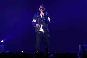 R. Kelly. Black man in black jacket and pants and hat in front of black and blue background