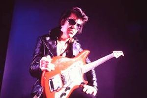 Link Wray. Indigenous man with black hair in black jacket and sunglasses and white shirt holds red and white electric guitar in front of black and navy background