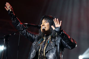 Buffy Sainte-Marie. Indigenous woman with black hair in black leather jacket and shirt and scarf performs behind black microphone and stand and in front of grey curtain under red lights.