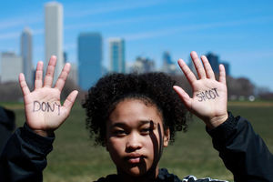 A young, Black student with curly hair and black jacket holds up her hands with skyline in background