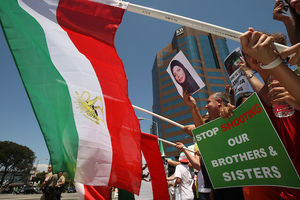 Iranian-American women and men and other Brown individuals hold green and red and white former Iranian flag with gold lion and green protest signs in front of blue sky and grey building.