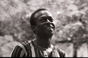 Miles Davis. Black and white photograph of Black man smiling in multicolored striped shirt in front of trees.