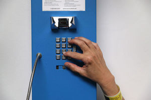 A closeup of a prisoner's hand as she dials numbers on a blue, public pay phone inside of a prison.