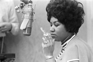 Aretha Franklin. Black and white photo of a Black woman turned to the side with a short, curled bouffant hairstyle smoking a cigarette in front of a microphone.