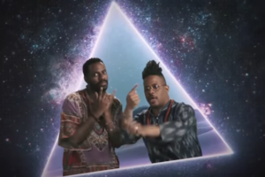 Open Mike Eagle and Baron Vaughn. Two Black men standing in front of a screen with a blue triangle and a starry night sky