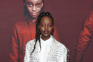 Lupita Nyong'o. A Black woman with long braids wearing a white shirt stands behind a large movie poster with a burgundy background with a photo of a little Black girl with straight hair and a red blouse.