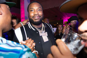 Black man with beard and platinum diamond encrusted chains smiles while looking slightly right is greeted by a group