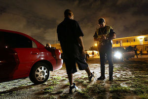 Black man stands next to a red car and in front of police officer as he takes a sobriety test at night.