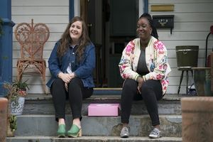 A white woman sits on the steps of a porch with her hands cupped between her knees and a black woman sits on the same porch on the right also with her hands cupped between her knees.