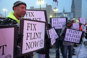 Black protestors holding signs to fix Flint